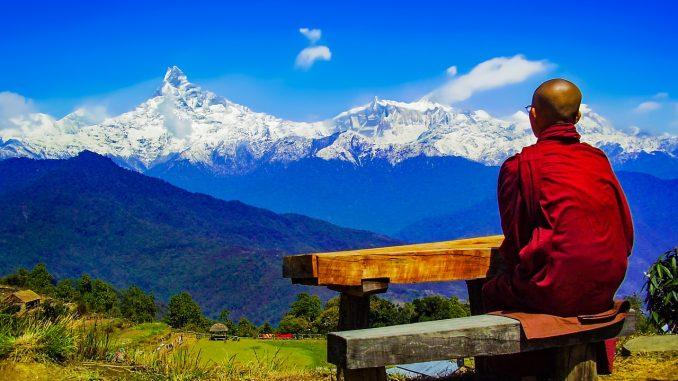 Un monje budista contemplando las montañas
